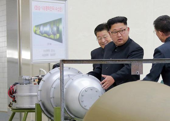 북한 김정은이 핵무기연구소를 방문해 핵탄두를 살펴보고 있다. 뒷편 설명판에 ICBM급인 '화성-14형 핵탄두(수소탄)'이란 글귀가 눈에 띈다. [조선중앙통신]