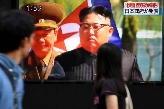 3일 북한이 6차 핵실험을 했을 가능성이 있다는 일본 정부의 발표를 전하는 옥외 TV 화면을 도쿄 시민들이 지나가며 지켜보고 있다. [도쿄 AFP=연합뉴스]