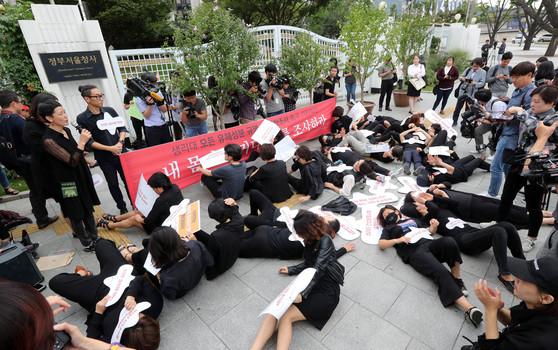 여성환경연대가 5일 정부서울청사 앞에서 생리대 유해성분 전수조사와 역학조사를 촉구하는 '내 몸이 증거다 나를 조사하라' 기자회견을 마치고 누워서 항의하는 퍼포먼스를 하고 있다. 강정현 기자