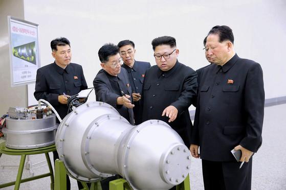 북한 조선중앙통신은 3일 핵실험에 앞서 김정은 노동당 위원장(왼쪽 넷째)이 핵무기 병기화 사업을 현지지도했다며 수소탄 개발을 주장하는 관련 사진을 공개했다. 사진에는 장구 형태의 핵폭발장치로 보이는 물체가 있다. 왼쪽 위엔 <화성-14>형 핵탄두(수소탄)이라고 쓰인 도면이 보인다. [사진 조선중앙통신]