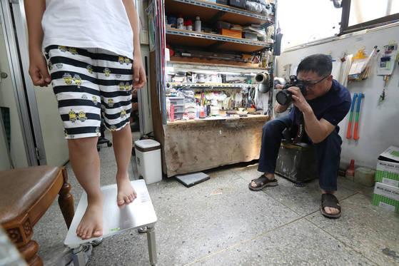인터뷰 도중 손님이 찾아왔다. 여름방학을 맞아 새벽부터 대전에서 달려온 꼬마 손님과 부부였다. 유오상(오른쪽) 삼덕스포츠 대표가 발모양 기록을 위해 사진 촬영하고 있다.우상조 기자