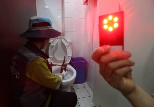 서울시 여성안심보안관이 청파동의 한 여성 화장실에서 전자파탐지기로 몰래카메라가 숨겨져 있는지 점검하고 있다. 김상선 기자
