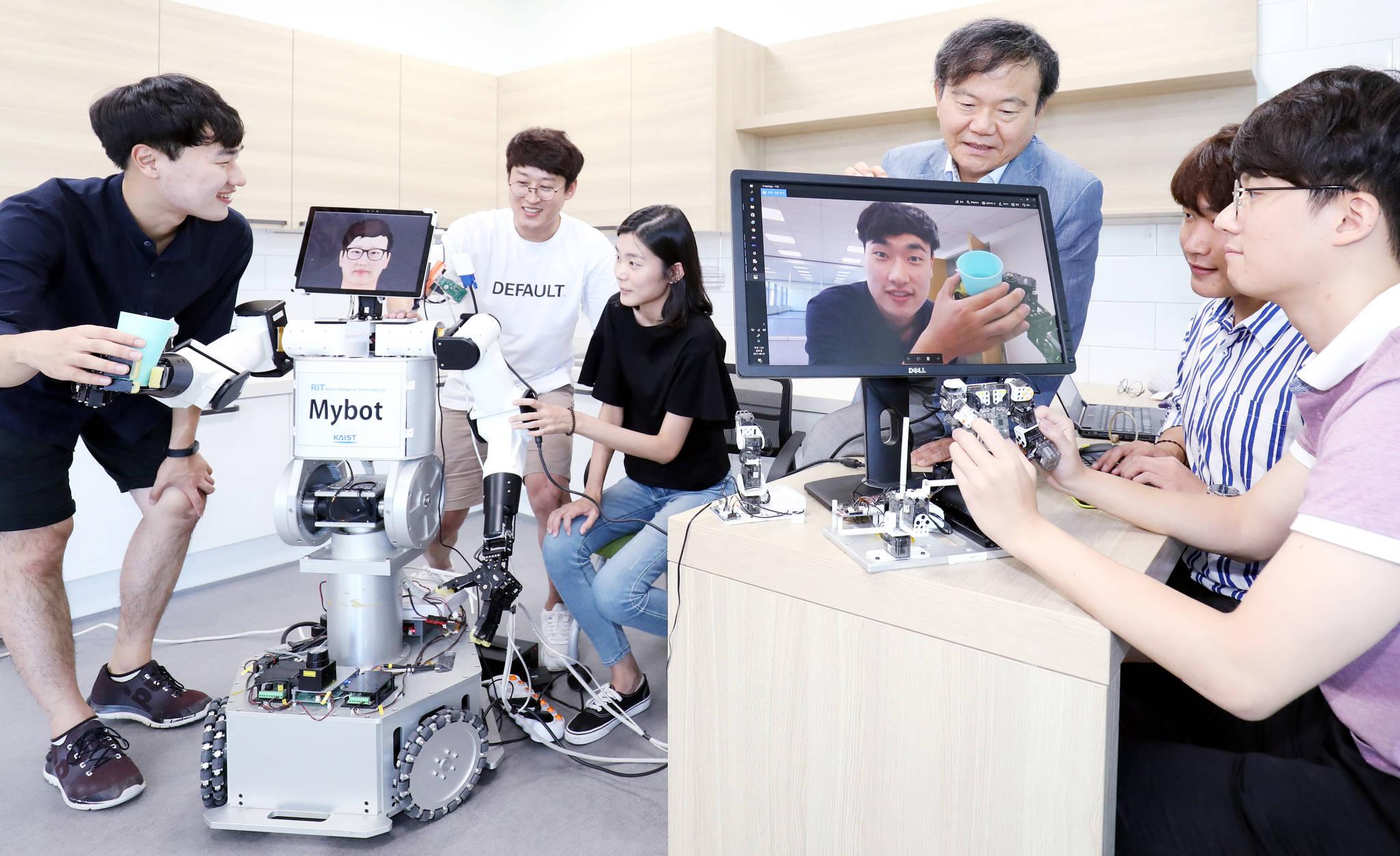 올해 전자공학과 평가에서 '최상'에 오른 KAIST 전기및전자공학부의 김종환 교수(오른쪽에서 셋째)가 지난 1일 학생들과 함께 사람 감정을 읽는 로봇인 '마이봇(Mybot)'의 작동 상태를 확인하고 있다. [프리랜서 김성태]