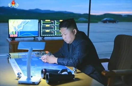 김정은이 옆 모니터에 화성-12형의 비행 궤도 등 정보가 나타나 있다. [사진 조선중앙TV]