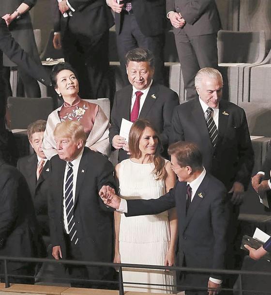 지난 7월 7일(현지시간) 독일에서 열린 주요 20개국(G20) 정상회의에서 각국 정상 내외가 엘브필하모니 콘서트홀 공연을 관람했다. 공연 시작 전 도널드 트럼프 미국 대통령(앞줄 왼쪽)이 문재인 대통령의 손을 꼭 잡고 있다. 뒷줄에 선 시진핑 중국 국가주석이 이를 물끄러미 바라보고 있다. [사진 중앙포토]