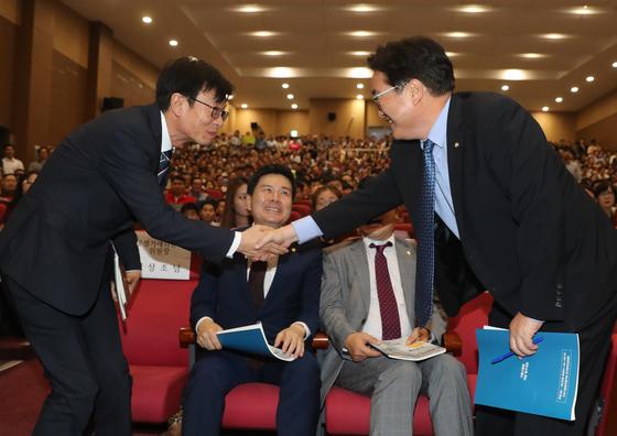 더불어민주당 우원식 원내대표(오른쪽)와 김상조 공정거래위원장이 6일 오후 국회 의원회관에서 열린 가맹사업법 개정촉구 대회에 참석해, 악수를 나누고있다. [연합]
