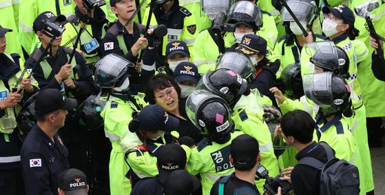 헬멧에 분홍색 스티커를 부착한 '여경팀'이 7일 오전 경북 성주군 소성리 마을회관 앞에서 집회 참가자들을 도로 밖으로 끌어내고 있다. [우상조 기자]
