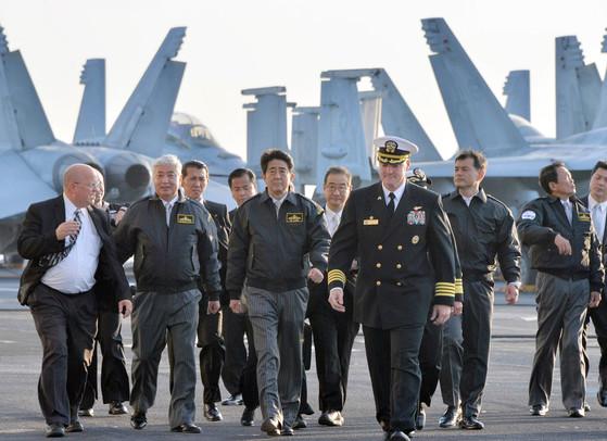 지난 2015년 아베 신조 일본 총리(왼쪽에서 세번째)가 가나가와현 앞바다 사가미만에서 미국 원자력 항공모함 로널드 레이건호에 탑승해 크리스 볼트(왼쪽에서 네번째) 함장의 안내를 받고 있다. 레이건함은 일본 요코스카항을 모항으로 두고 있다. [사진 지지통신]