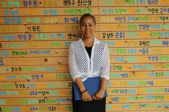 해밀학교 후원자 이름이 새겨진 벽 앞에서 웃고 있는 해밀학교 이사장 인순이. [사진 위스타트]