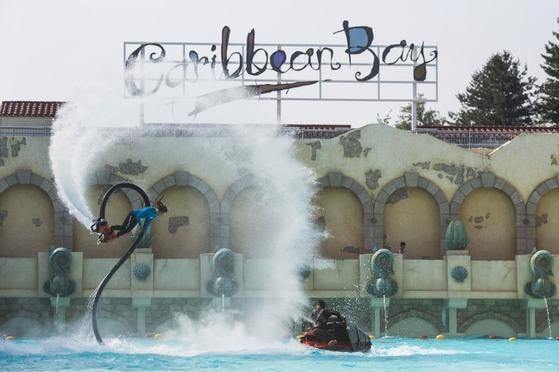 공중제비돌기를 선보이고 있는 박진민씨.제트스키(오른쪽)의 엔진에서 공급받은 에너지를 조절해 수면 위 최고 20m 높이까지 날아오를 수 있다. [사진 에버랜드]