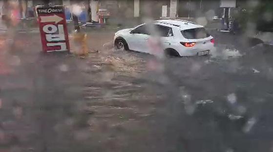 부산 지역에 호우 경보가 내린 11일 오전 부산 사상구 학장동의 한 도로가 침수돼 출근길 시민들이 불편을 겪고 있다. [연합뉴스]