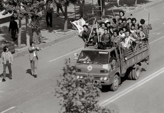 광주민주화운동에 관한 최초의 기록서『죽음을 넘어 시대의 어둠을 넘어』에 수록된 1980년 5월광주의 사진. 무장한 광주 시민이 태극기 꽂은 트럭을 타고 이동하고 있다. [사진 나경택, 창비]