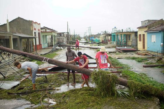9일(현지시간) 허리케인 어마가 할퀴고 지나간 쿠바 동부 지역 주민들이 무너진 전봇대를 피해 다니고 있다. [쿠바 로이터=연합뉴스]