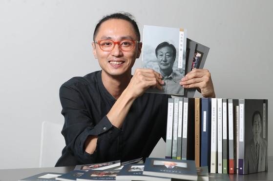 12일 서울 순화동 월드컬처오픈 회의실에서 자서전을 앞에 놓고 사진을 찍은 박범준 '꿈틀'편집장. 손에 들고 있는 책중 맨 앞에 있는 책이 그의 아버지 자서전이다. [신인섭 기자]