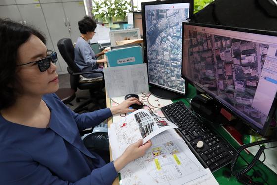 서울시 건축기획과 김정훈 주무관이 13일 불법으로 증개축된 건물있는지 항공사진과 평면사진을 비교 분석하고 있다. 모니터는 특수제작된 3D모니터로 3D안경을 쓰고 보면 건물이 입체적으로 도드라져 보여진다.김경록 기자