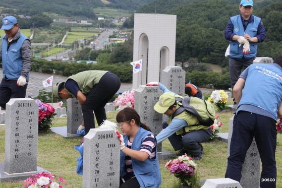 16일 오전 포스코 냉연부 소속 직원들이 경북 영천에 있는 국립영천호국원에서 비석을 닦고 있다. [사진 포스코]