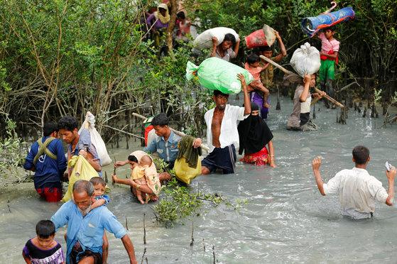미얀마에서 쫓겨난 무슬림 로힝야족 난민들이 국경을 넘은 뒤 강을건너 이웃 방글라데시의 난민촌으로 이동하고 있다. [로이터=연합뉴스]