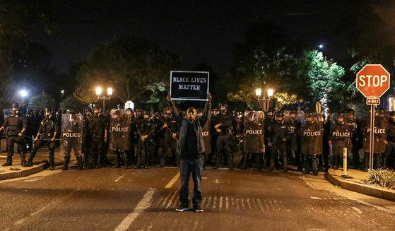 15일(현지시간) 흑인 생명도 중요하다'는 피켓을 든 흑인이 진압경찰과 맞서고 있다. [로이터=연합뉴스]