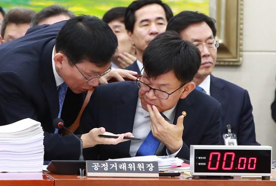 18일 오전 국회 정무위원회 전체회의에 참석한 김상조 공정거래위원장(오른쪽)이 답변준비를 하고 있다.[연합]