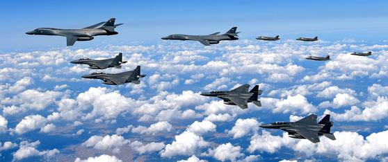지난 18일 미국 공군의 전략폭격기 '죽음의 백조' B-1B 2대(왼쪽 위)와 해병대 소속 스텔스 전투기 F-35B 4대(오른쪽 위)가 한국 공군 F-15K 전투기 4대와 한반도 상공에서 연합훈련을 했다. [사진제공=공군]