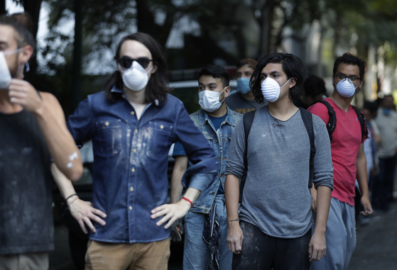 Volunteers wearing dust masks wait in line to pass out rubble as rescue workers search inside a collapsed building in the Condesa neighborhood of Mexico City, Tuesday, Sept. 19, 2017. A 7.1 earthquake stunned central Mexico, killing more than 100 people as buildings collapsed in plumes of dust.(AP Photo/Rebecca Blackwell)