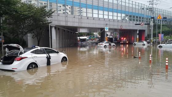 부산지역에 폭우가 내린 11일 부산 연제구의 한 아파트 단지 앞 도로가 물에 잠겨 차량이 침수 피해를 겪고 있다. [부산소방안전본부 제공=연합뉴스]