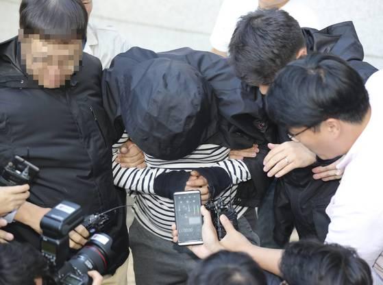 20일 오후 충북 청주시 흥덕경찰서에서 20대 여성을 살해한 뒤 옷을 벗겨 유기한 혐의(살인)로 긴급 체포된 A씨(32)가 취재진의 질문에 침묵하고 있다. [연합뉴스]