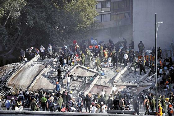 19일 지진으로 무너진 멕시코시티의 한 건물에서 주민들과 경찰·군인·소방대원 등이 합심해 피해자들을 구조하고 있다. [멕시코시티 AFP=연합뉴스]