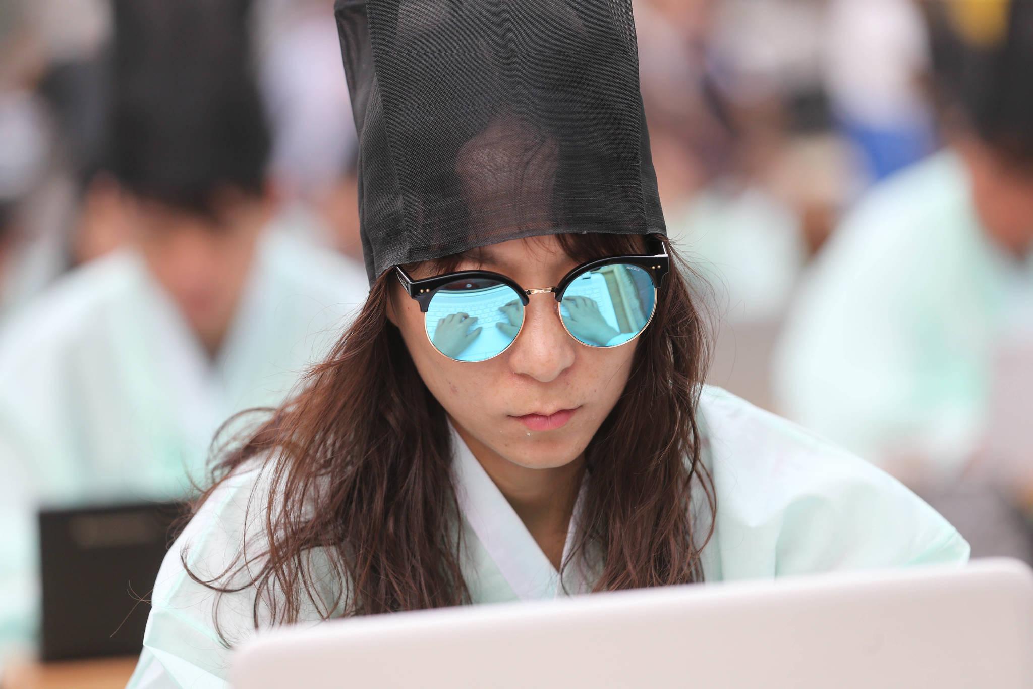 디지털 백일장 참가자 선글라스에 노트북 자판 위에 놓인 손이 비치고 있다. 신인섭 기자