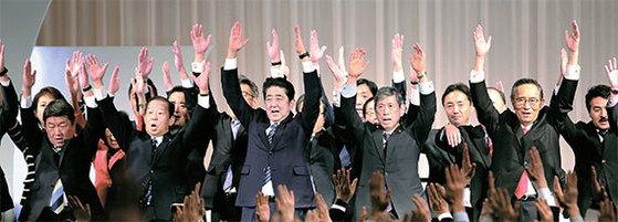 아베 신조(安倍晋三·가운데) 일본 총리가 5일 열린 자민당 전당대회에서 의원들과 만세를 부르고 있다. 이날 자민당이 총재 임기를 기존 '2연임 6년'에서 '3연임 9년'으로 연장하는 개정안을 가결함으로써 아베 총리는 2021년까지 장기집권이 가능해졌다. 아베 총리는 내년 9월 당 총재 선거에서 이기고 2019년 11월까지 재임하면 역대 최장수 총리가 된다. [도쿄 AP=뉴시스]
