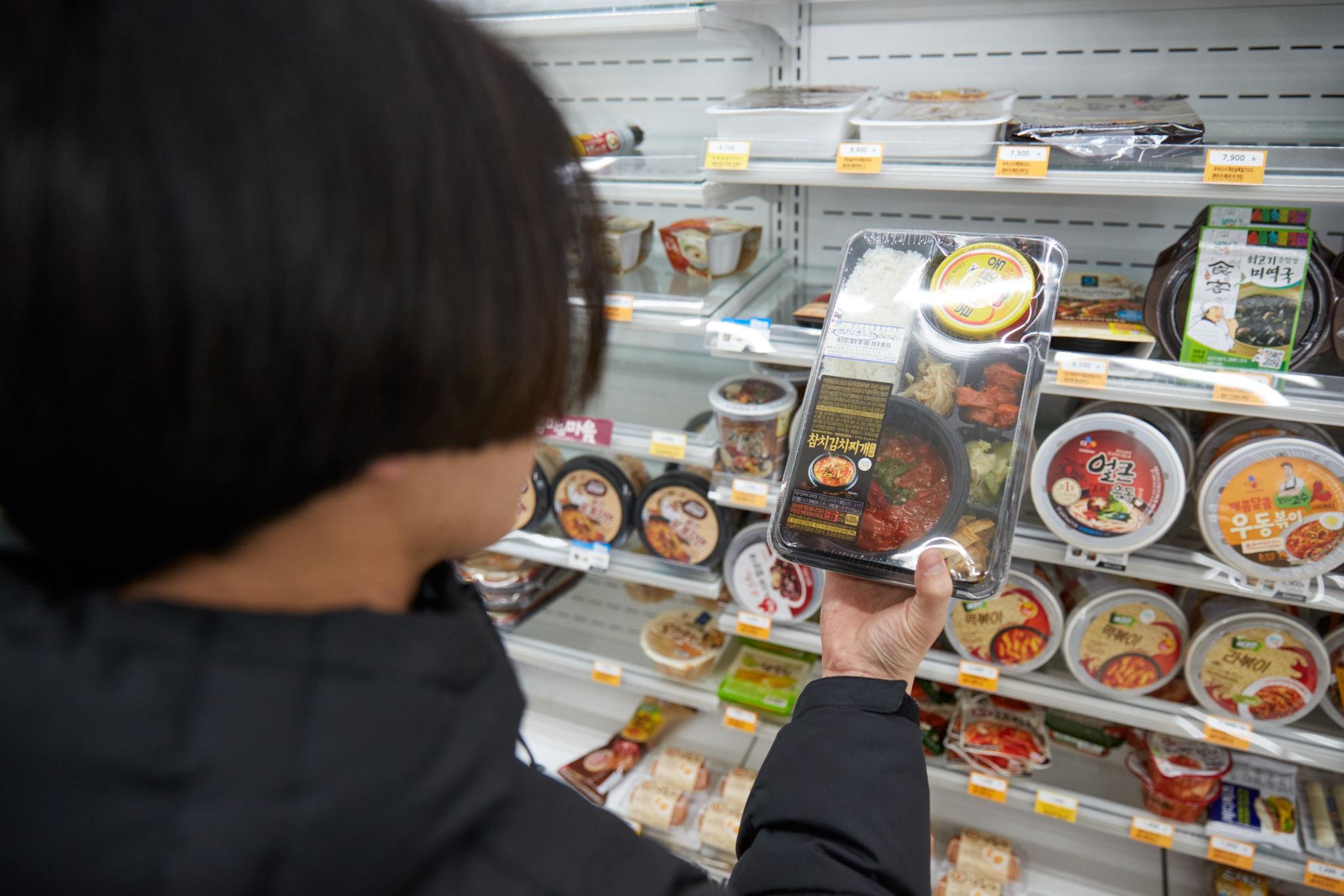 편의점 진열대에서 도시락을 꺼내 보고 있는 한 남성. 영양성분 표시가 의무화되면 제품을 구매하기 전에 영양소가 어떻게 되는지 확인할 수 있다. [중앙포토]