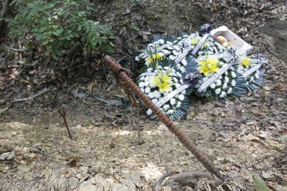 '개구리소년 유골 발견 15주기' 추모식이 26일 오전 대구시 달서구 와룡산 세방골 자락에서 열렸다. 유골이 발견된 지점에 어린이들의 죽음을 애도하는 꽃이 놓여 있다. 법의학팀이 유골을 발굴하던 자리에 쇠말뚝이 남아 있다. 프리랜서 공정식