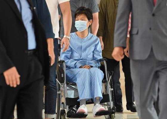 지난 8월 30일 박근혜 전 대통령이 허리 질환 치료차 서울 서초동 서울성모병원에서 진료를 받은 뒤 환자복을 입고 휠체어를 탄 채 병원을 빠져 나가고 있다. [연합뉴스]