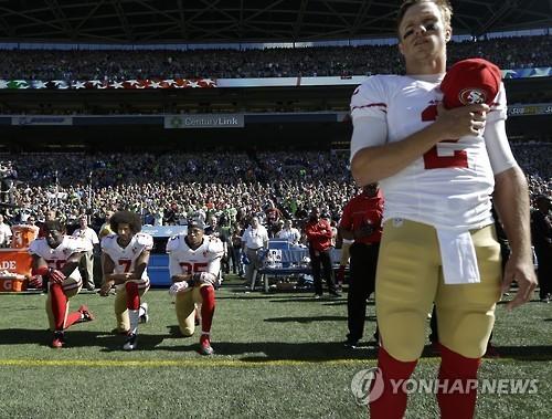 지난해 국기에 대한 경례를 하는 다른 선수들과 달리 무릎을 꿇은 콜린 캐퍼닉(가운데). [AP=연합뉴스]