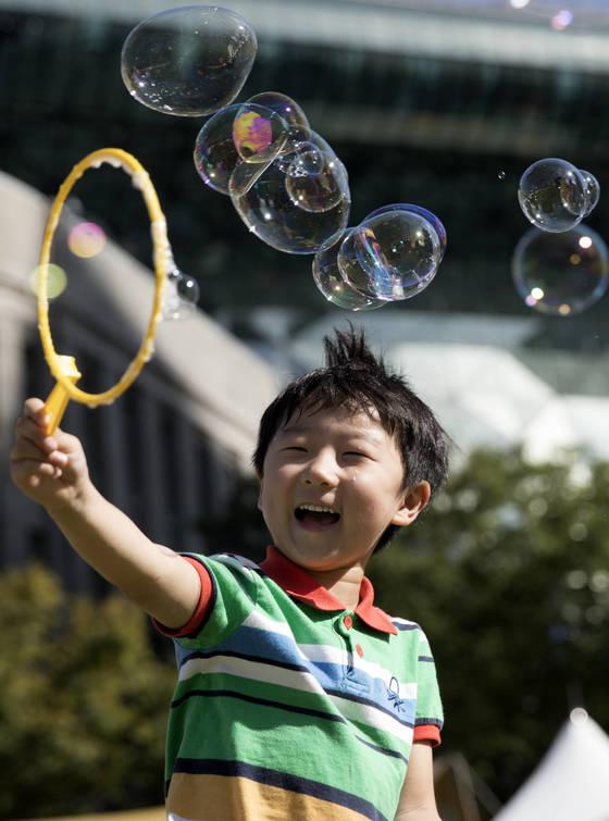 조기교육 연령이 점점 낮아지면서 어린이들의 '놀 권리'에 대한 관심도 높아지고 있다. 16일 오전 서울광장에서 열린 '서울시민 건강한마당'에서 한 어린이가 비눗방울 놀이를 하고 있다. [연합뉴스]