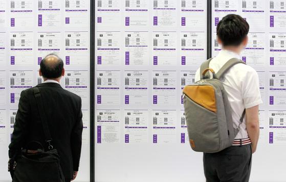 한 중년 남성과 청년이 취업 게시판을 살펴보고 있다. [중앙포토]