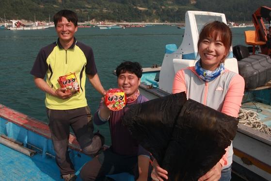 너구리에 들어있는 다시마 생산지인 금일도의 어민들이 너구리와 다시마를 들고 있다 [사진 농심]