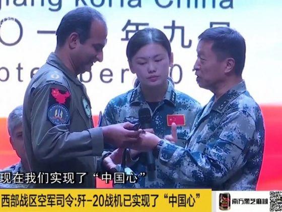 """잔허우순(戰厚順) 서부전구 공군 사령관이 최근 중국-파키스탄 공군의 '슝잉(雄鷹·독수리)-Ⅵ' 연합 훈련 폐막식에서 파키스탄 지휘관에서 젠-20 모형을 선물하고 있다. 잔 사령관은 """"젠-20은 이미 '중국심(中國心)'을 실현했다""""며 엔진 국산화를 인정했다.[사진=선전위성방송 캡처]"""