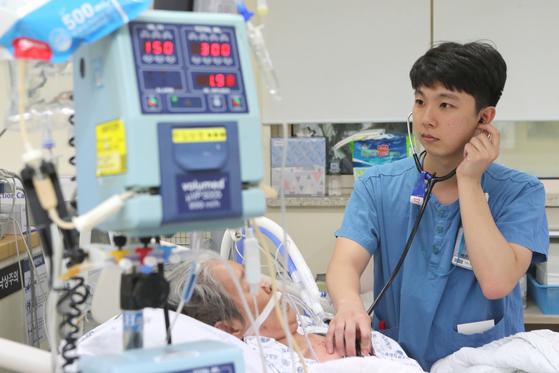 지난달 29일 서울대병원 중환자실에서 구태형 간호사가 환자를 돌보고 있다. 외과계 중환자실엔 수술 뒤 상태가 불안정한 환자가 많아 세심히 살펴야 한다. 구씨는 연휴 기간 7일을 출근한다. [최정동 기자]