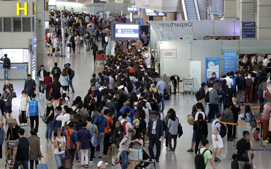 역대 최장인 올해 추석연휴를 앞두고 28일 오전 인천공항에서 여행객들이 출국게이트 앞에 길게 줄서고 있다. [연합뉴스]