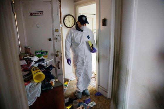 조지 벨 소유의 아파트를 둘러보며 시신의 신원을 확인하기 위해 노력하는 검시관. [사진 뉴욕타임스]