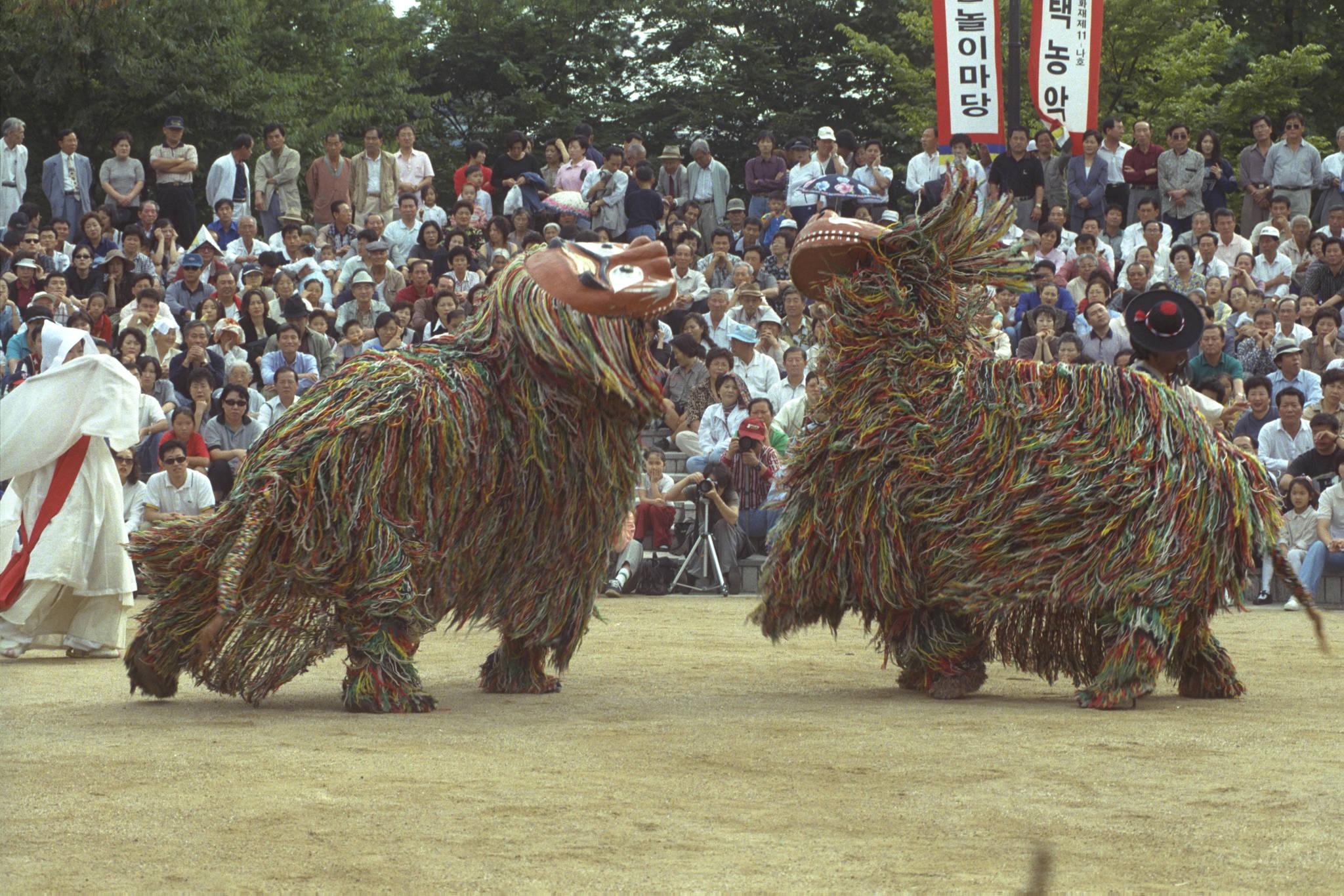 1998년 추석 연휴 마지막날인 10월 6일 시민들이 서울놀이마당에서 열린 민속공연 '북청사자놀이'중 병신춤 장면을 보며 즐거워하고 있다.[중앙포토]
