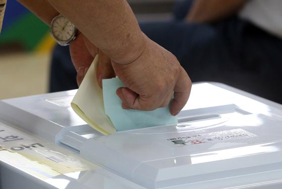 제7대 지방선거가 내년 6월 13일 개최된다. 사진은 지난 2014년 6·4 지방선거 때 서울 종로구 가회동 제1투표소가 마련된 재동초등학교에서 한 시민이 투표를 하는 모습. [연합뉴스]