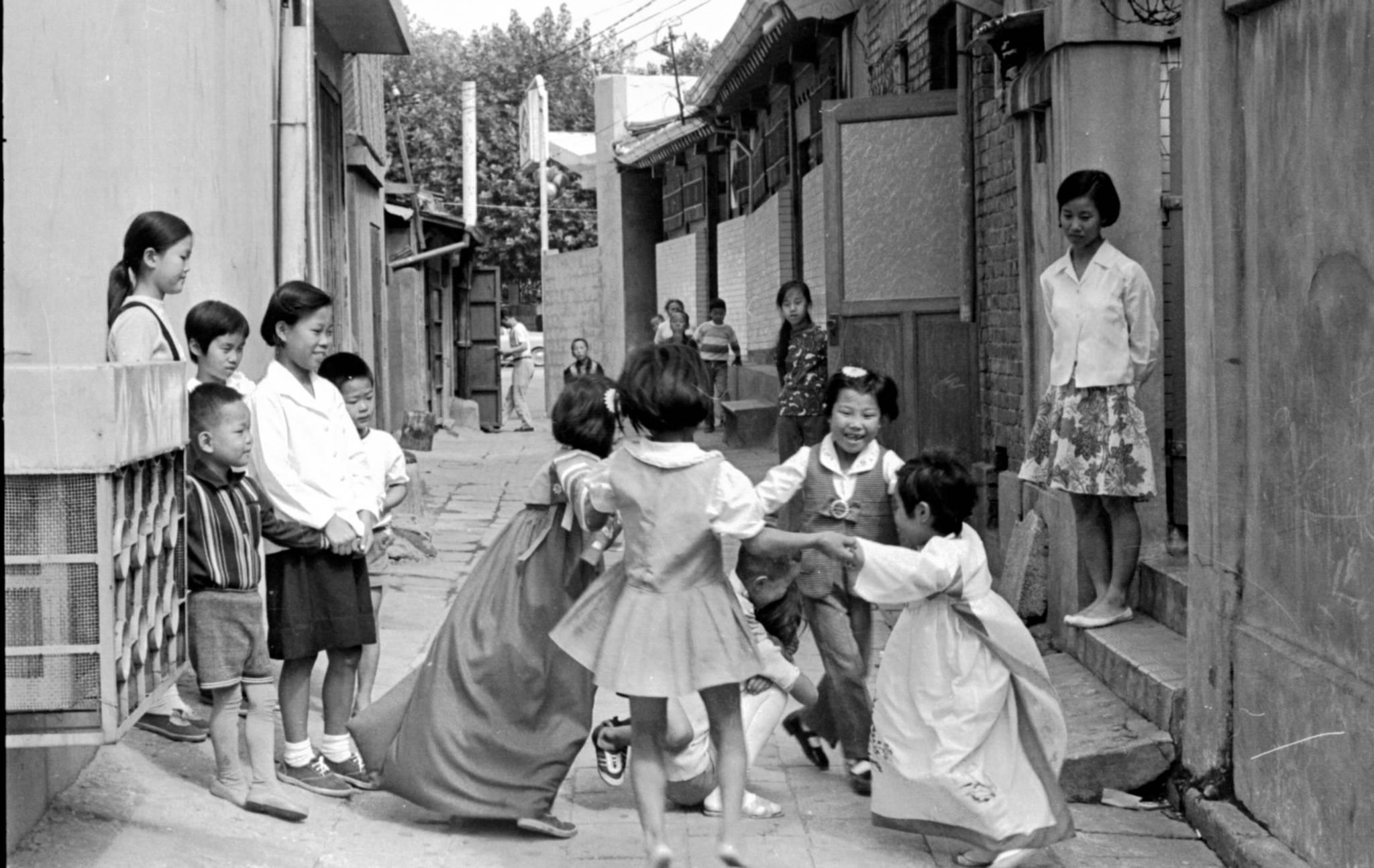 놀 것과 놀 장소가 마땅치 않았던 당시는 동네 골목이 놀이터였다. 한복도 귀한 때라 골목길에 한복을 입은 어린이가 17명 중 두명밖에 보이지않는다.[중앙포토]