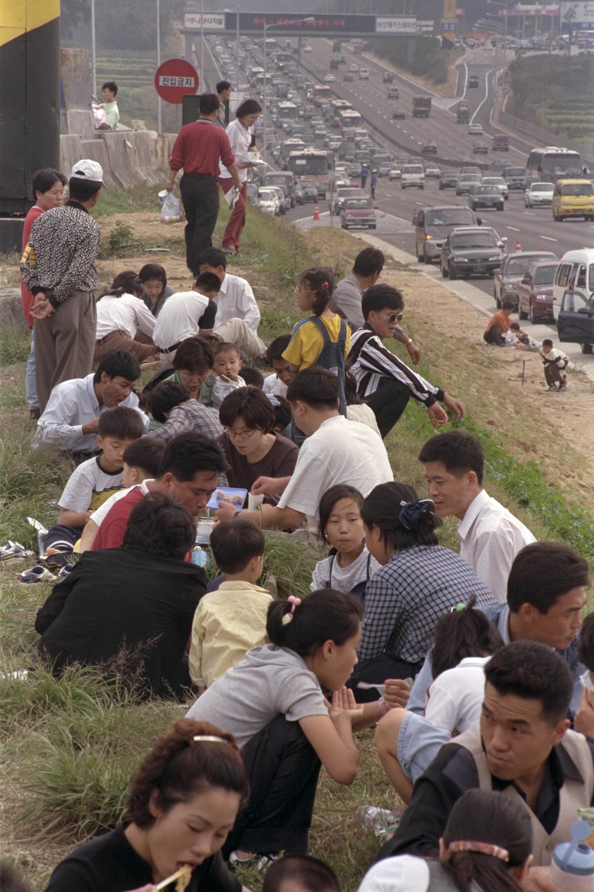 1998년 10월 6일 오후 고속도로가 귀경차량으로 정체를 반복하고 휴게소가 혼잡하자 귀경객들이 길가에 차를 세우고 음식을 먹고 있다.[중앙포토]