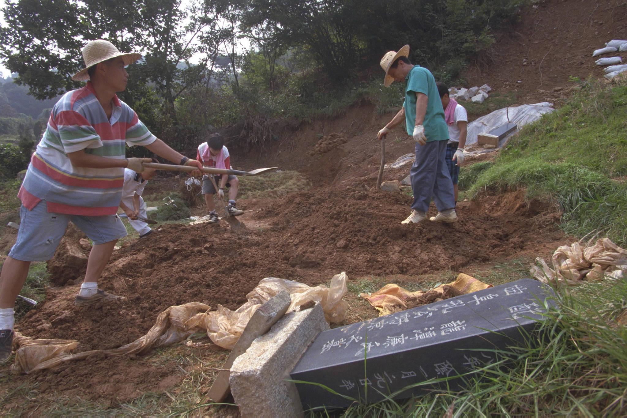 1998년 9월 27일 경기도파주시용미리 시립묘지를 찾은 한가족이 전달인 8월 집중호우에 훼손된 묘지를 복구하느라 분주하게 움직이고 있다.[중앙포토]