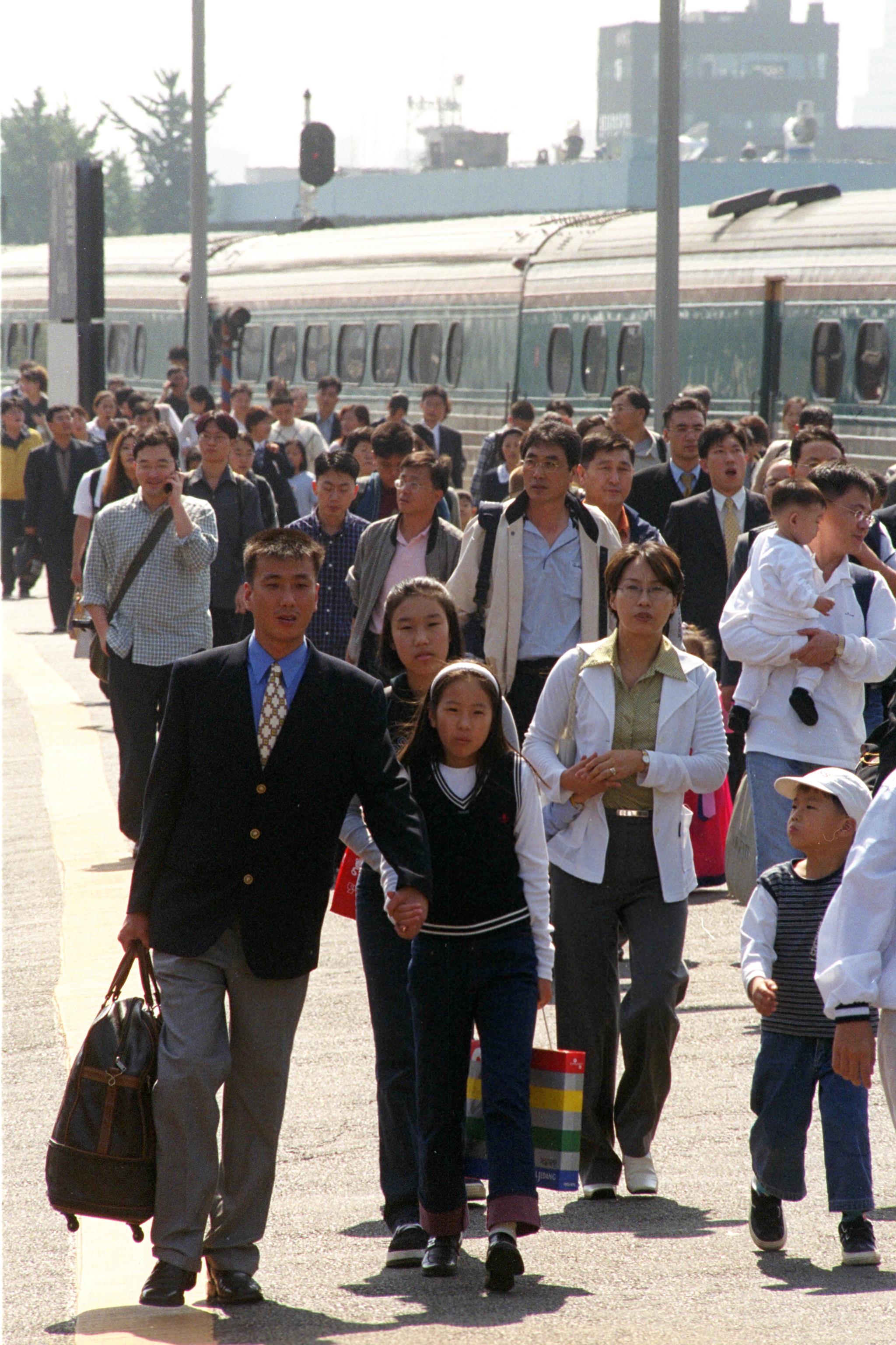 1999년 추석연휴(9월 23~26일) 마지막날인 26일 오후 고향의 정이 가득 담긴 선물 보따리를 든 귀경객들이 밝은 표정으로 서울역 플랫폼을 빠져나오고 있다.[중앙포토]