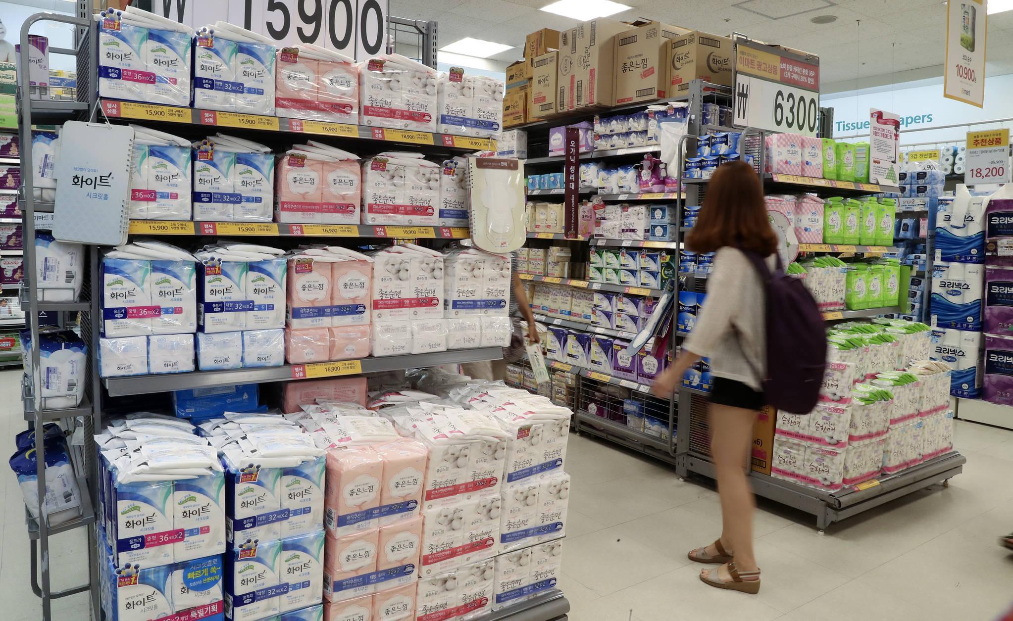 생리대가 진열된 서울의 한 대형마트 매장 사이로 여성 소비자가 지나가고 있다. [중앙포토]