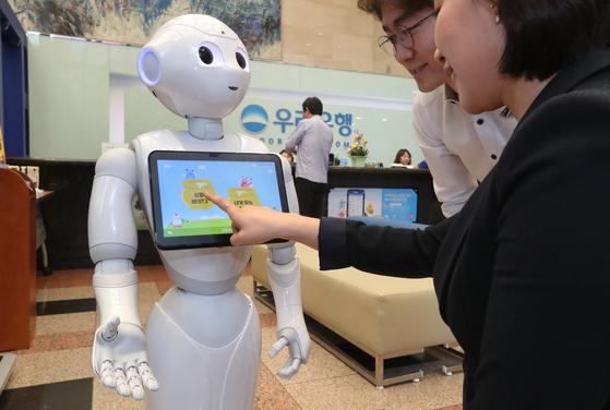 우리은행은 11일 금융권 최초로 소프트뱅크의 AI 로봇행원 페퍼를 영업장에 배치했다.이날 오전 로봇행원 페퍼가 서울 회현동 우리은행 본점영업장에서 금융상품을 안내하고 있다.최승식 기자