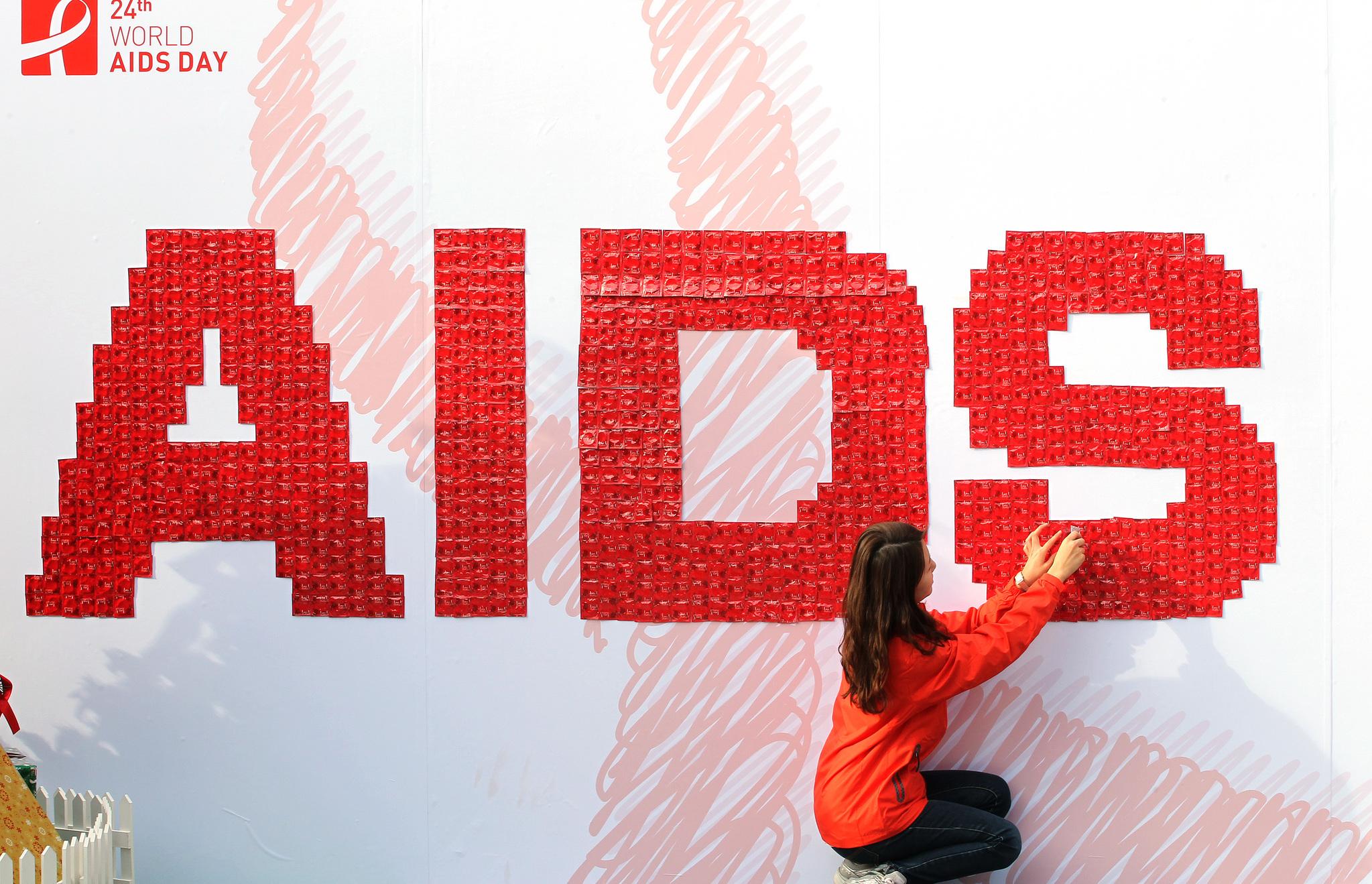 한국에이즈퇴치연맹 관계자가 에이즈 예방을 위한 퍼포먼스 차원에서 붉은 콘돔으로 `AIDS' 영문 글자를 만들고 있다. [연합뉴스]